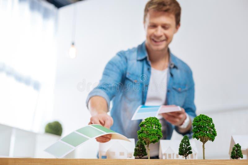 Tillfredsställd tekniker som bötfäller den bästa färgen för ett hus och le fotografering för bildbyråer