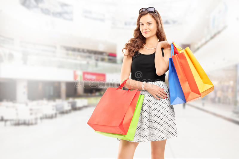 Tillfredsställd ung kvinna som poserar med shoppingpåsar i en galleria arkivbilder