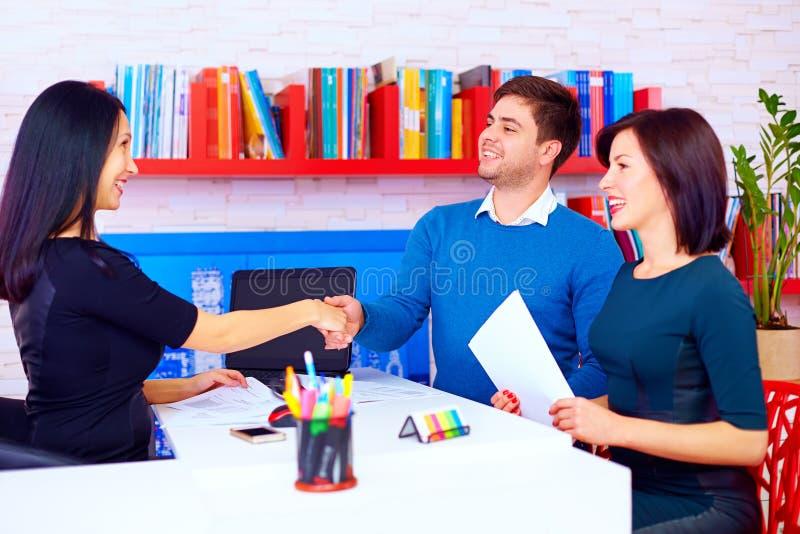 Tillfredsställda klienter, par efter lyckade affärsförhandlingar i regeringsställning arkivfoto