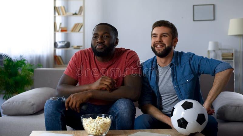 Tillfredsställda vänner som håller ögonen på fotbollsmatchen på stor tv, segra för landslag arkivbild
