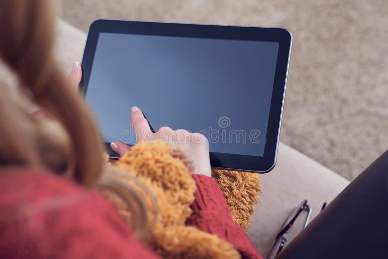 Tillfredsställer det hållande ögonen på massmedia för ung kvinna handlag ett tomt minnestavlaskärmsammanträde på en soffa hemma arkivfoton