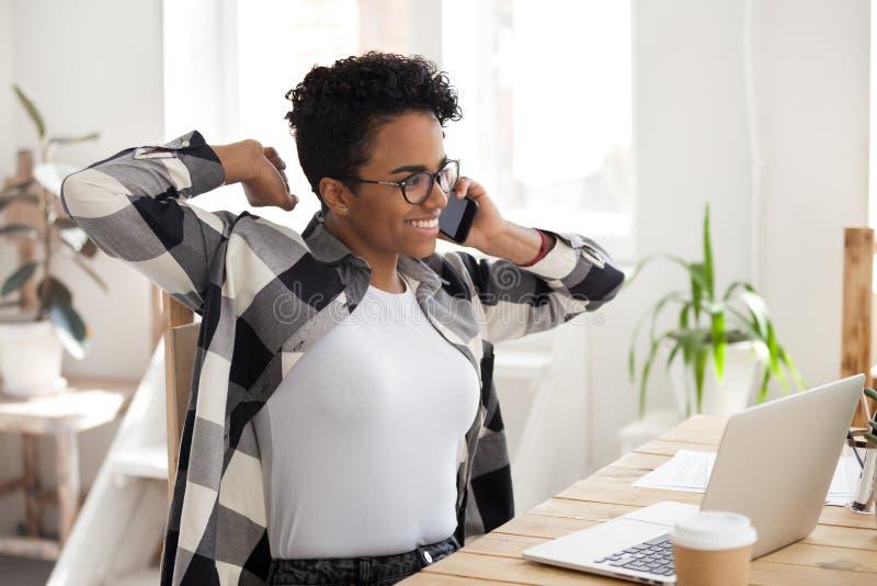 Tillfredsställt afrikanskt kvinnasamtal vid telefonen, lyckligt fullföljande som arbetar royaltyfria bilder