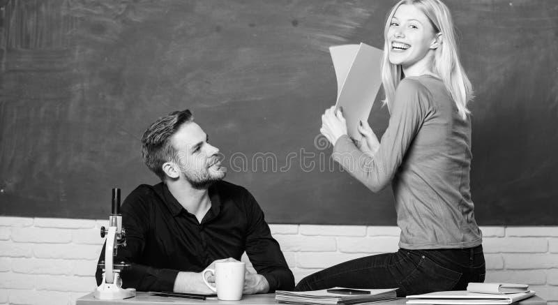 Tillfredsst?llt med hennes fl?ckar Par som studerar i klassrum N?tt l?rare och stilig l?rare som graderar legitimationshandlingar royaltyfri fotografi