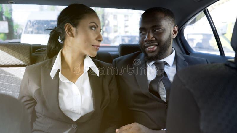 Tillgiven affärskvinna och man som flörtar i bilen, kontorsromans, angelägenhet royaltyfria bilder