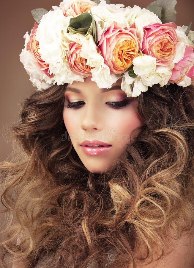 Tillgiven flicka i krans av färgrikt drömma för blommor arkivfoto