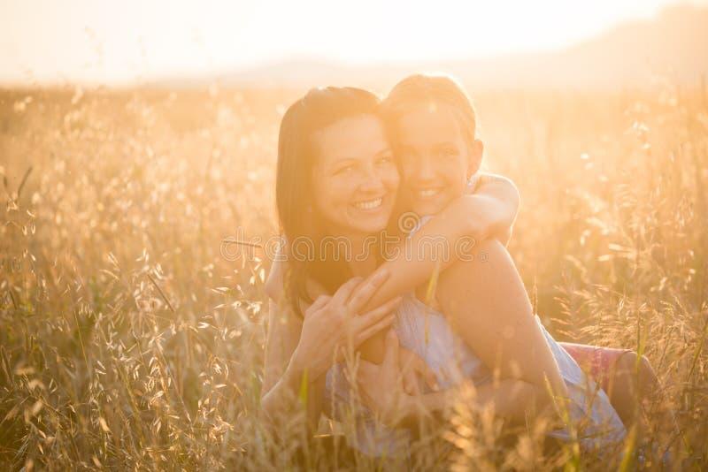 Tillgiven ung dotter som kramar hennes moder arkivfoton