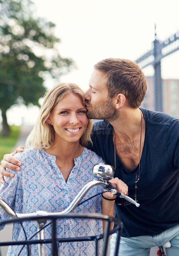 Tillgiven ung man som kysser hans flickvän arkivfoto