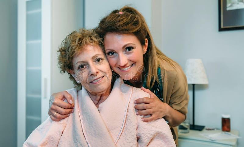 Tillgiven vaktmästare som poserar med den äldre patienten royaltyfria foton