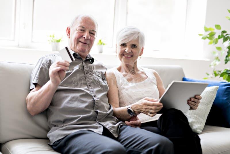 Tillgivna attraktiva äldre par som tillsammans sitter på en soffa med bärbara datorn och kreditkorten arkivfoto