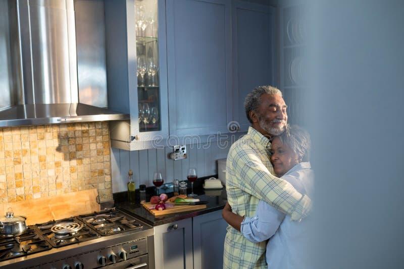 Tillgivna le par som omfamnar, medan stå i kök royaltyfri foto