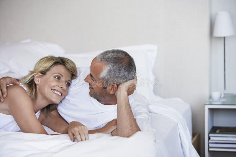 Tillgivna par som kopplar av på säng royaltyfri foto