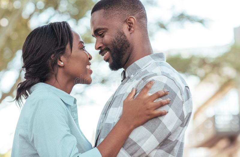 Tillgivna unga afrikanska par som tillsammans utanför står royaltyfria foton