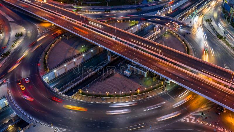 Tillkrånglad genomskärning för väg i staden på natten med rörelse för medelbilljus, flyg- sikt royaltyfri foto