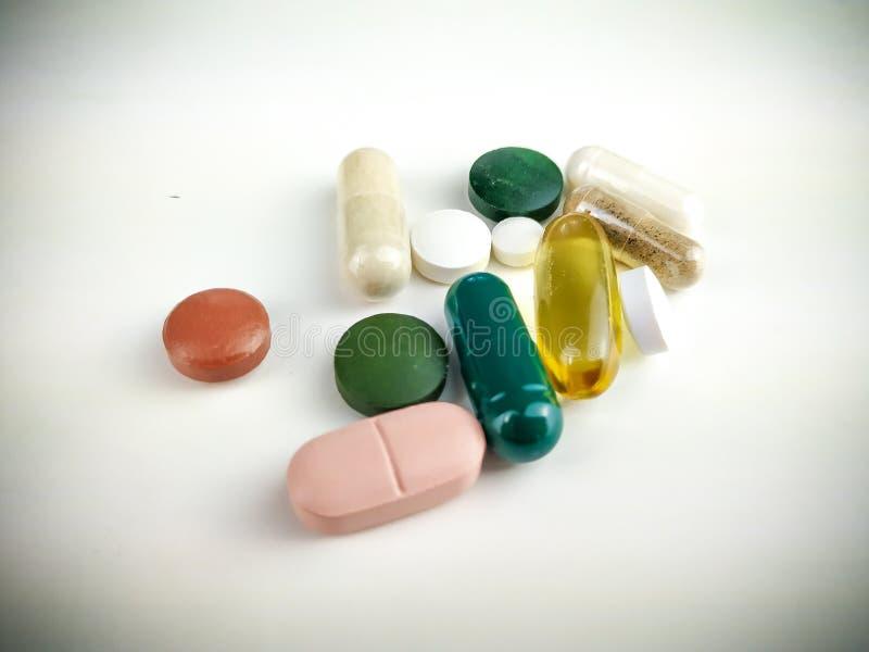 Tillsättning av olika tabletter, tabletter och kapslar till vita bakgrundsbilder som en hälsosam prevention och dosering av vitam royaltyfri bild