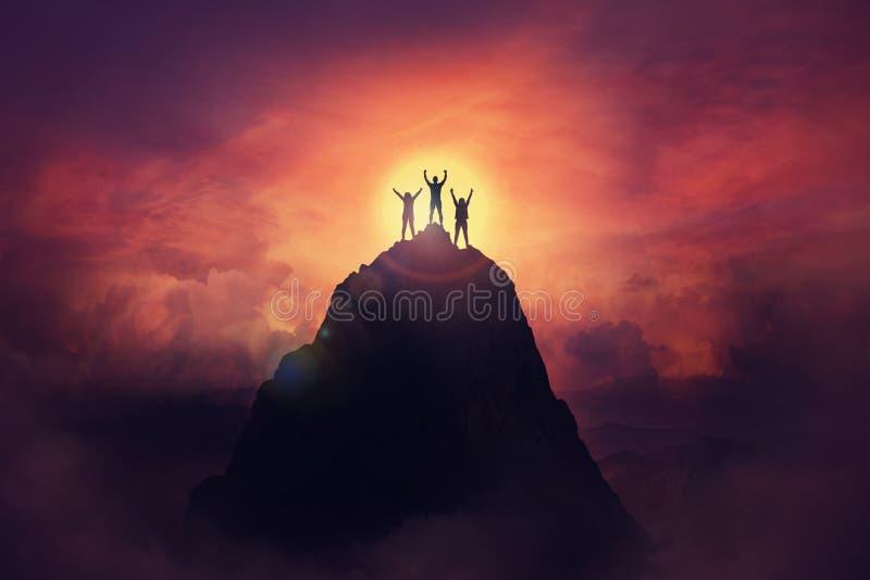 Tillsammans för att övervinna hinder som en grupp bestående av tre personer som höjer upp händerna på toppen av ett berg Fira seg royaltyfria bilder