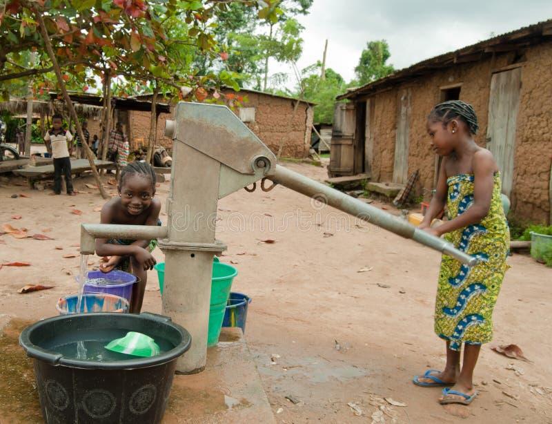 Tilltalande vatten för afrikanskt lantligt flickabarn arkivbilder