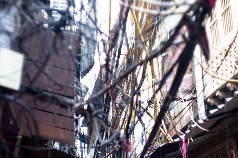 Tilltrasslade smutsiga elektriska trådar på polen som poserar en säkerhetsfara royaltyfri fotografi