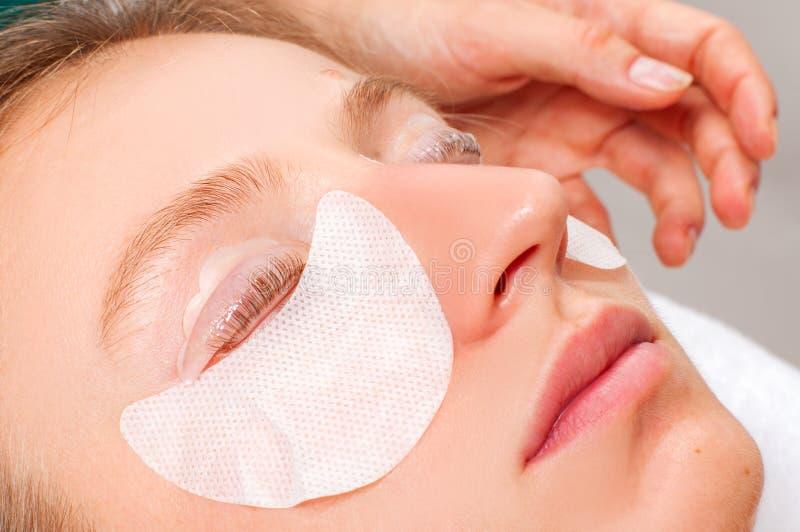 Tillvägagångssätt för ögonfransomsorgbehandling Kvinna som gör den ögonfranslamination, att befläcka, att krulla, att plätera och arkivbilder