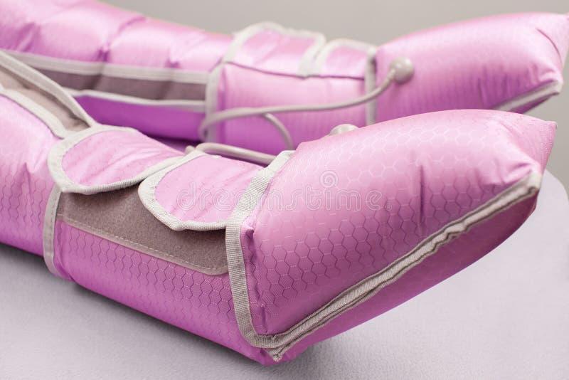 Tillvägagångssättet av tryckterapi för viktförlust Kvinna i en dräkt för en massage under tillvägagångssättet arkivbild