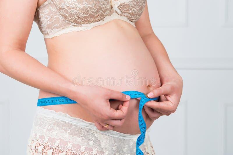 Tillväxt av behandla som ett barn Den härliga gravida flickan med långt hår mäter beloppet av mage royaltyfri fotografi