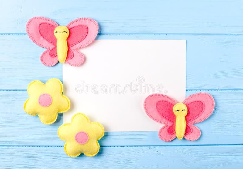 Tillverka rosa färger och gulna fjärilen och blommor med vitbok, copyspace på blå träbakgrund Hand - gjorda filtleksaker Göra sam arkivfoto