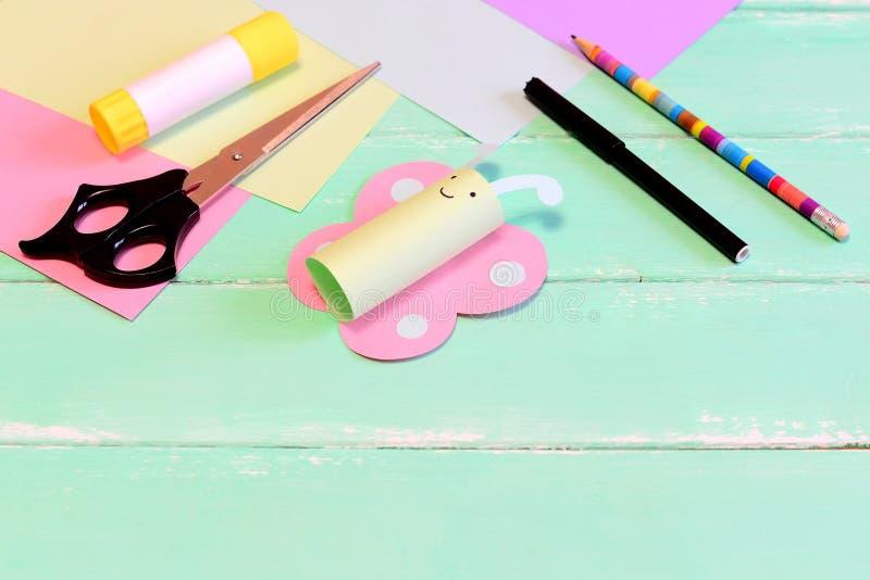 Tillverkar den pappers- fjärilen för gyckel, sax, markören, limpinnen, färgat papper, blyertspenna på den gröna trätabellen Hjälp arkivfoton