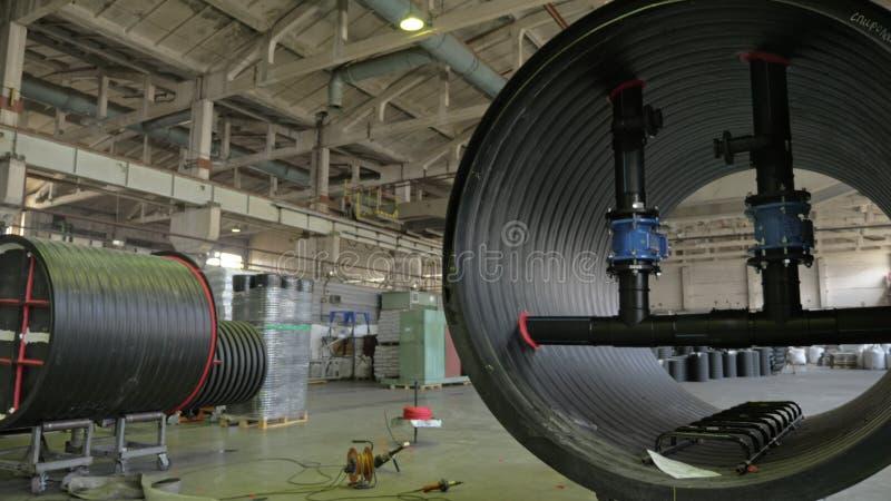 Tillverkning av plast- vattenrör Sikt av fabriksgolvet Färdigt stort rör Processen av plast- rör för danande royaltyfri foto