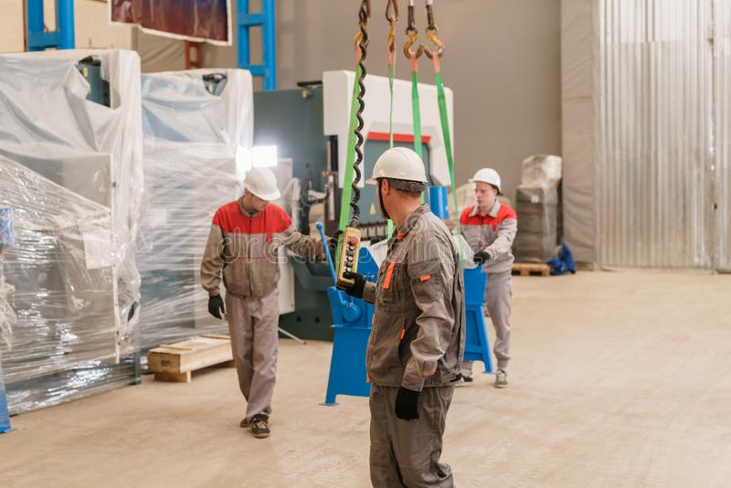 Tillverkningseminarium flytta kranen med strålen Arbetare justerar maskinen i lagret Produktionen av arkivbild