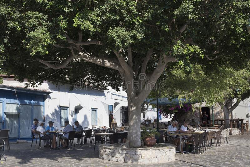Tilos island  - Outdoors traditional cafe bar in the shadow of the plane tree. Dodecanese Islands, Greece. Tlos island, Greece - September 22, 2018. Livadi stock photo