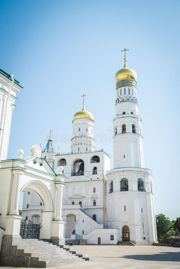 Tilt down on Ivan the Great Bell Tower cathedral inside Moscow Kremlin with clouds and blue sky in background.  stock photos
