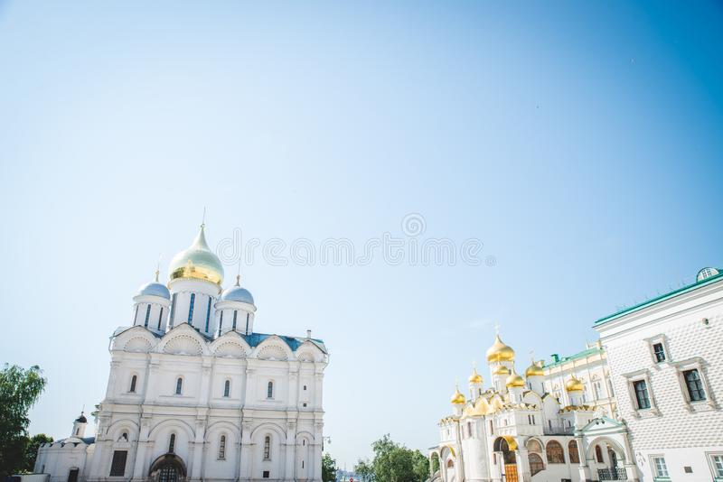 Tilt down on Ivan the Great Bell Tower cathedral inside Moscow Kremlin with clouds and blue sky in background.  stock images