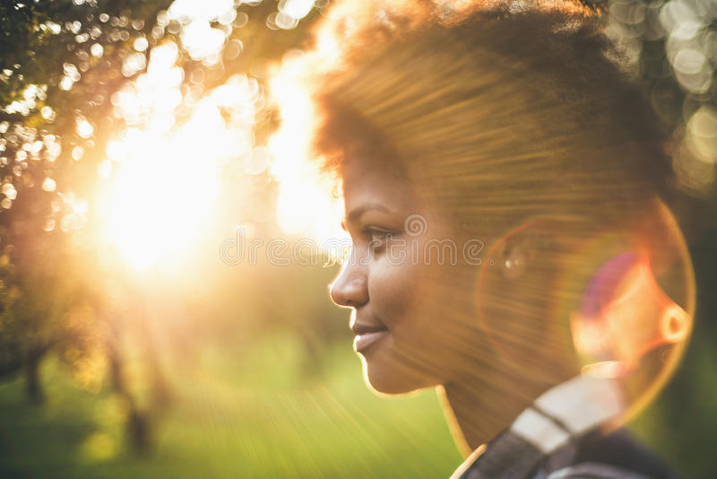 Tilt-shift portrait of black girl in front of sunset. Art tilt-shift portrait of young charming black girl with curly afro hair illuminated with sun backlight royalty free stock photos