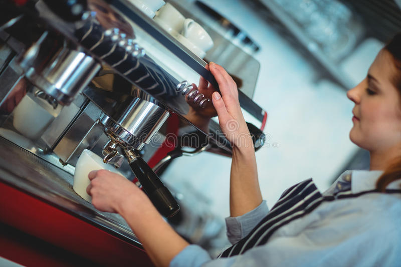 Tilt shot of barista using espresso machine to pour coffee in cup royalty free stock images