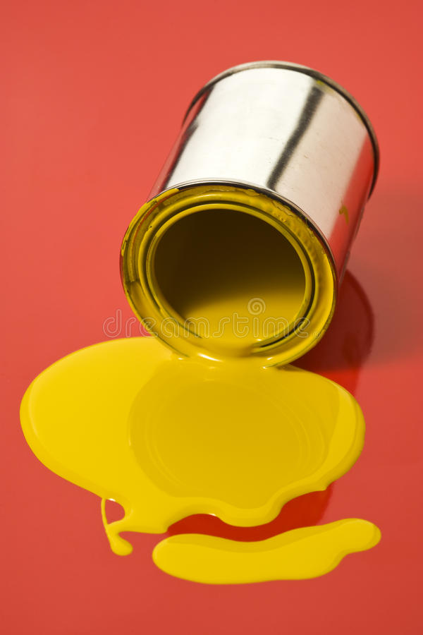 Tilted can with yellow paint on red surface. Yellow paint can tilted and leaking on red surface stock photos