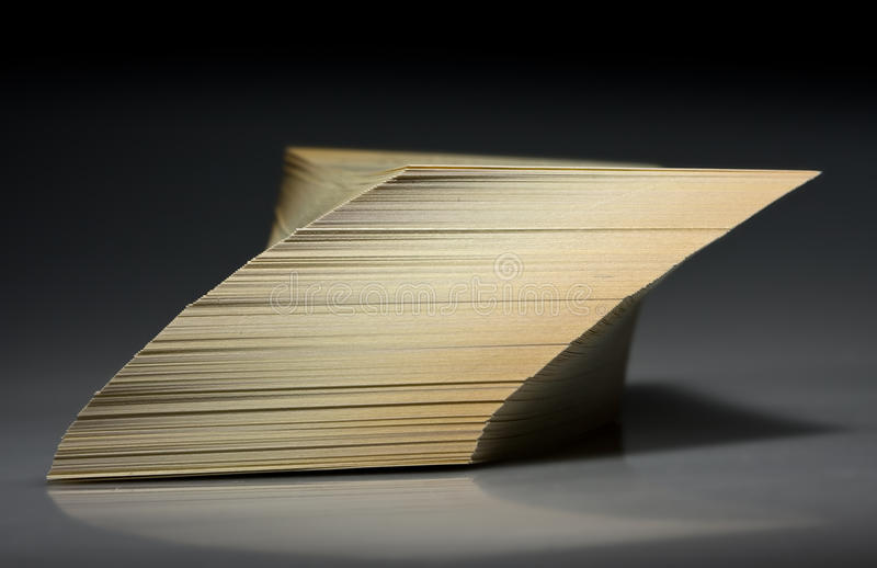Tilted cards stack. Shifted and tilted paper stack over black stock images