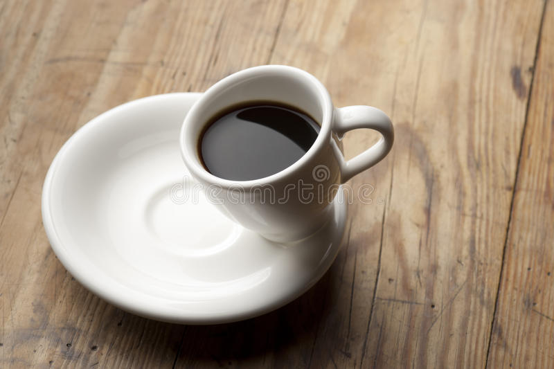Tilted coffee cup. Coffee in tilted white porcelain coffee cup stock photography