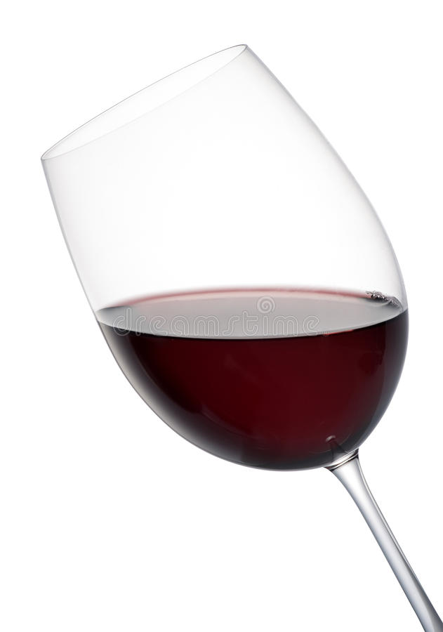 Tilted elegant glass of red wine. Tilted elegant stemmed glass of red wine isolated on white for a romantic evenings entertaining stock images