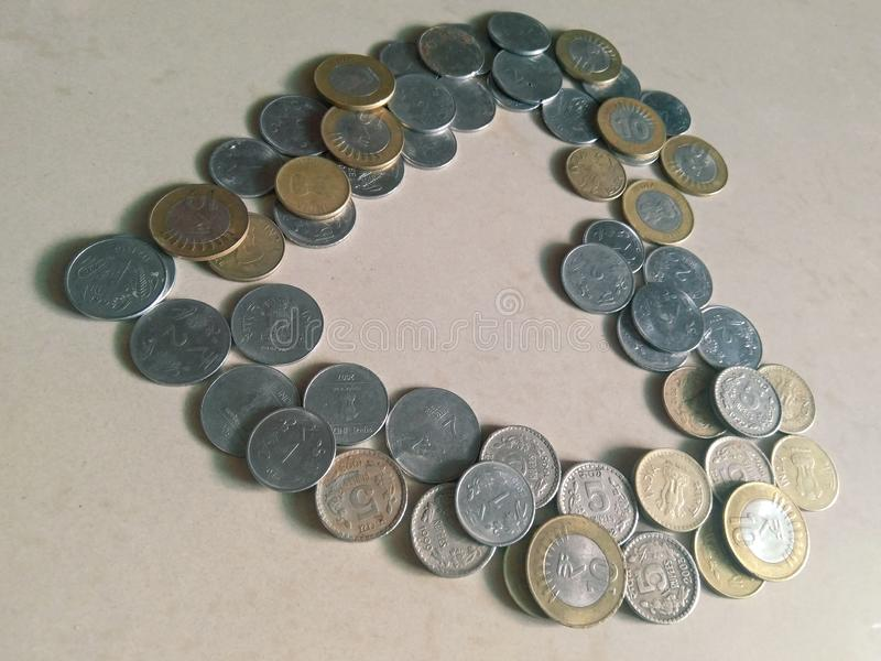 Tilted heart shaped structure made with Indian currency coins in a white marble background stock image
