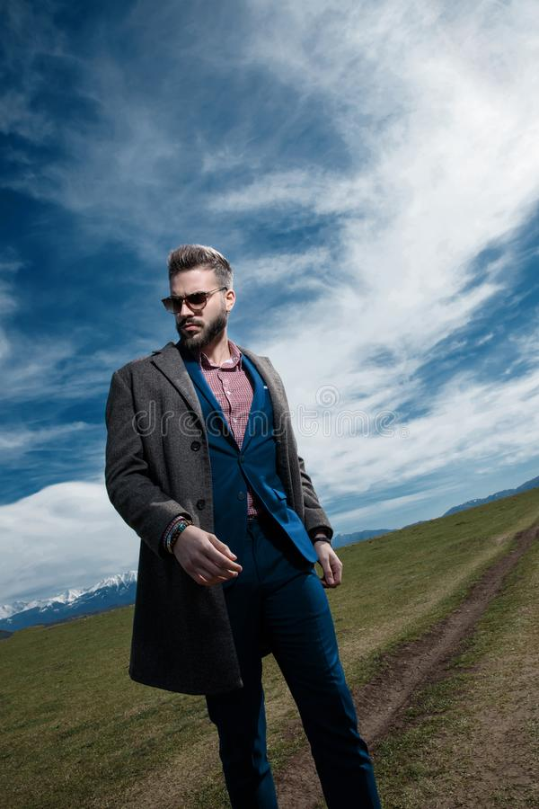 Tilted portrait of a serious looking man walking. And staring to the side while wearing sunglasses, a gray coat and a blue suit on outdoor background stock photos