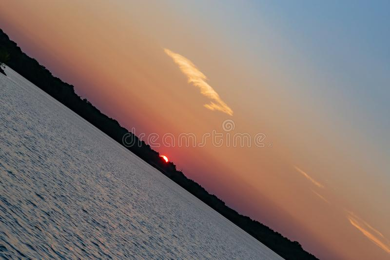 Clear outline of the setting sun at Sunset with beautiful skyline over lake Zorinsky Omaha Nebraska. Tilted skyline of the setting sun as it goes down on the royalty free stock images