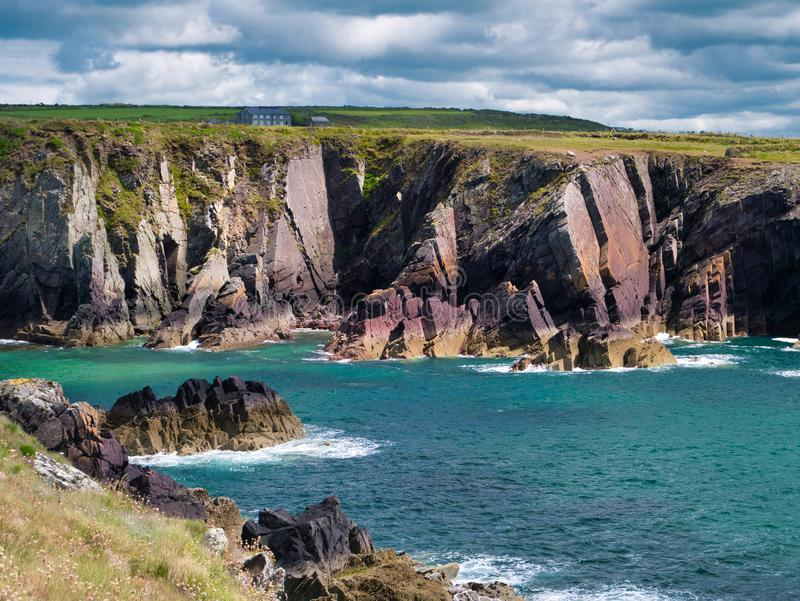 Tilted strata of red sandstone sedimentary bedrock cliffs in Pembrokeshire, Wales, UK. Tilted strata of red sandstone sedimentary bedrock cliffs from the stock photos