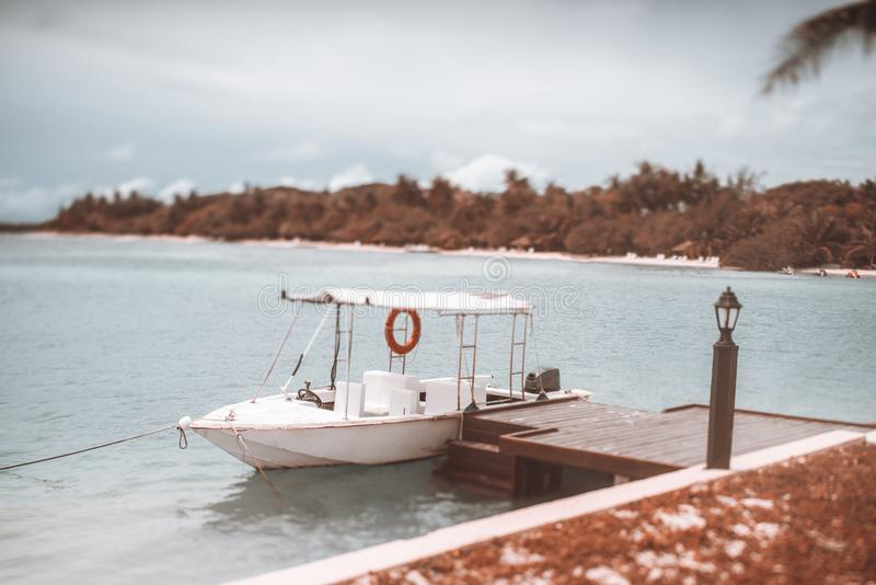 Tiltshift view of a white moored motorboat with marquee stock photos