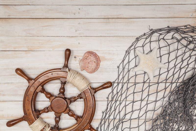 Timón del barco, cuerda y cáscara del mar en fondo de madera fotos de archivo