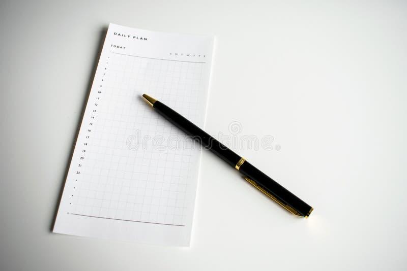 Tim- dagligt plan som gör listan med den svarta pennan fotografering för bildbyråer