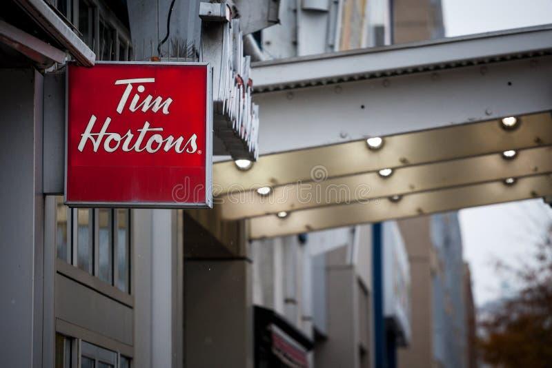 Tim Hortons logo framme av en av deras restauranger i Montreal, Quebec Tim Hortons är ett kanadensiskt märke för kafé och för fas royaltyfri bild