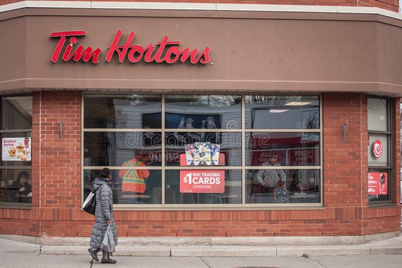 Tim Hortons logo framme av en av deras restauranger i Ottawa, Ontario, med att förbigå för gångare royaltyfri bild