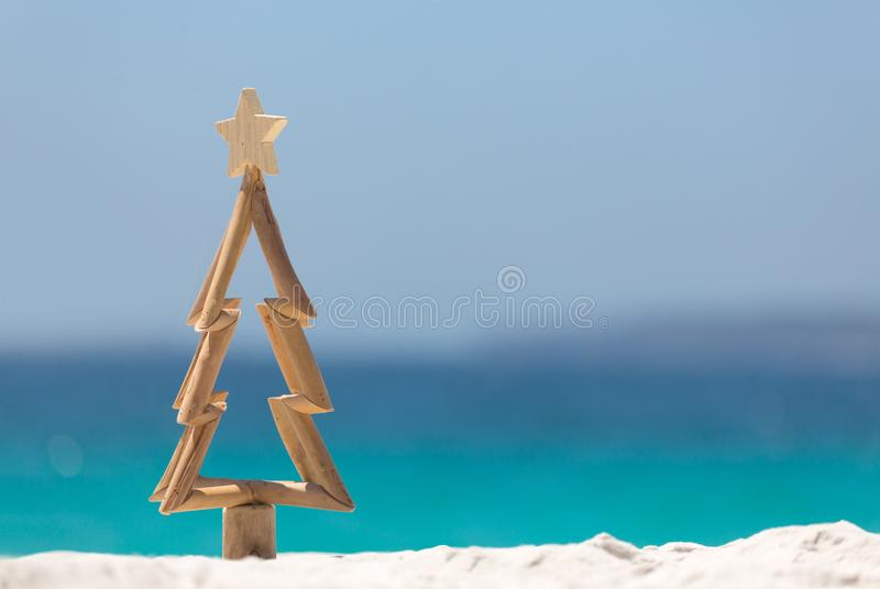Timber Christmas tree in sand on the beach stock photos