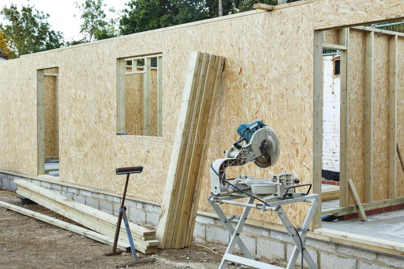 Timber frame house. A timber frame house is constructed using OSB sheets to form timber panels. Carpenters chop saw in the foreground stock images
