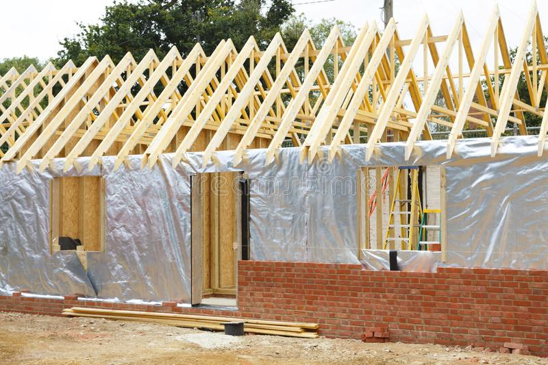 Timber frame house under construction. Timber frame house extension or annexe under construction with modern foil insulation and exterior brick wall stock image