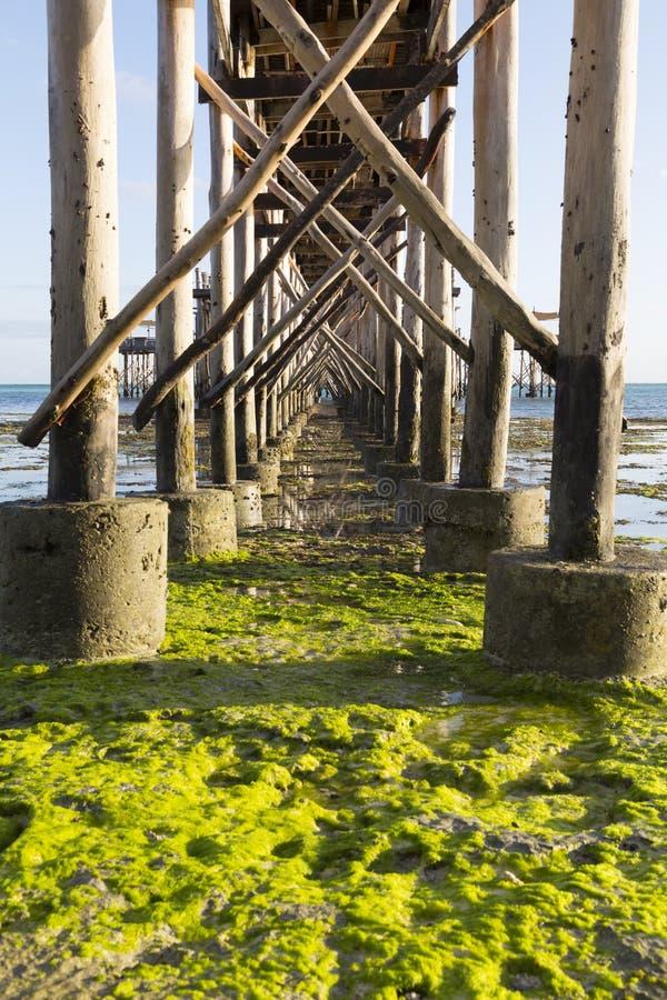 Timber piles of wooden pedestrian bridge above the ocean stock photo